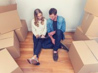 Young couple sitting in new house with packing boxes. They look like they have just moved in and they are very happy, smiling and talking. They are using a digital tablet, sitting on the floor in casual clothes. Copy space.